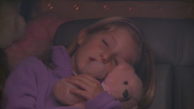 Holland, MichiganGirl sleeping in car holding teddy bear