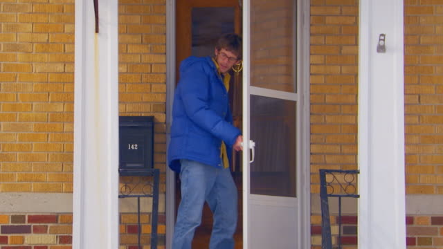 holland, michiganguy walking out of house - door knocker stock videos & royalty-free footage