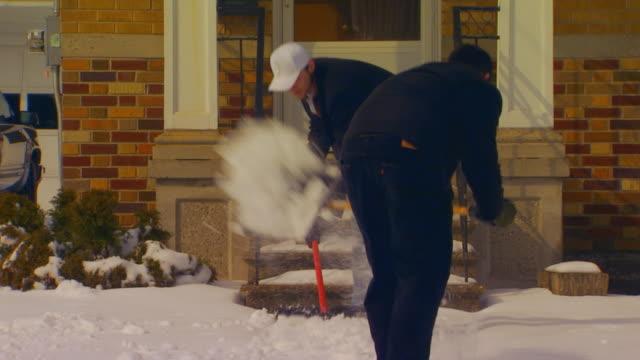vídeos de stock e filmes b-roll de holland, michigantwo guys shoveling snow - pá para neve