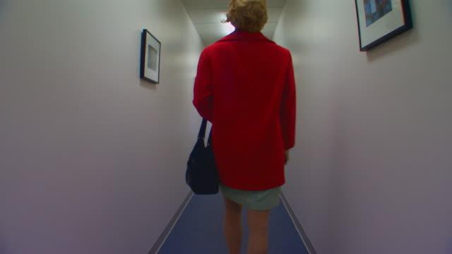 vídeos de stock, filmes e b-roll de holland, michiganwoman walking down a hallway and out the door - vista traseira