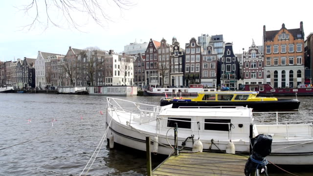 Holland Netherlands view. Street and Amsterdam canal, bicycles and cyclists, houseboats, living boats.