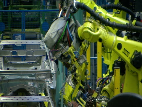Hollow car chassis move forward on automated production line robotic arms punch rivetting steel causing sparks to fly