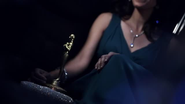 Hollywood actress with awards trophy leans on her man in back of limousine at awards show