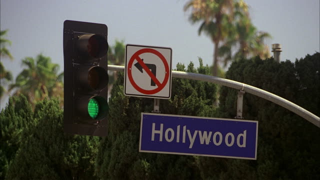 a hollywood boulevard street sign hangs near a stop light in los angeles, california. - road sign stock videos & royalty-free footage