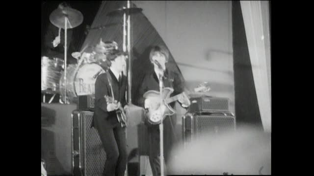 vídeos de stock e filmes b-roll de hollywood bowl fans chase beatles in their car as the travel to the hollywood bowl original footage of the world famous beatles performing live in a... - the beatles