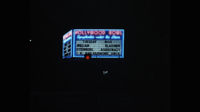 hollywood bowl sign at night showing william steinberg conducting the la philharmonic with valdimir askenazy hollywood hills los angeles california... - gewerbliches schild stock-videos und b-roll-filmmaterial