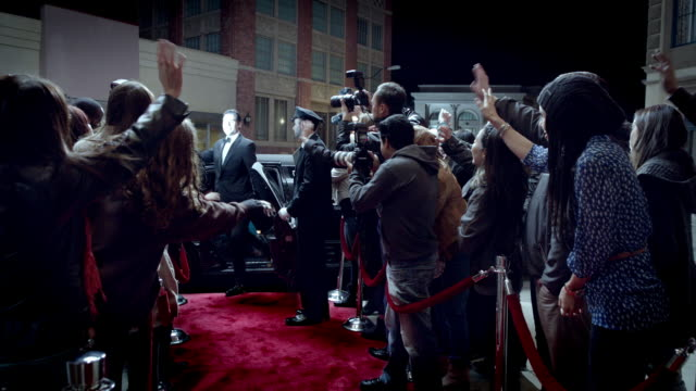 Hollywood couple climb out of limousine and greet fans and paparazzi on crowded red carpet at awards show