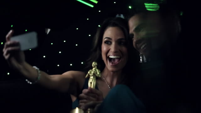vídeos de stock e filmes b-roll de hollywood couple in limousine snap silly photos with awards trophy at awards show - prémio