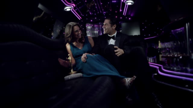 hollywood couple in limousine with awards trophy smile and wave to fans at awards show - husband stock videos & royalty-free footage