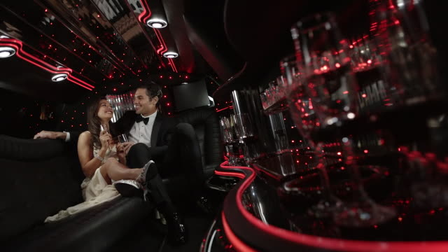 Hollywood couple recline in limousine, wave to fans, and clink champagne glasses at awards show