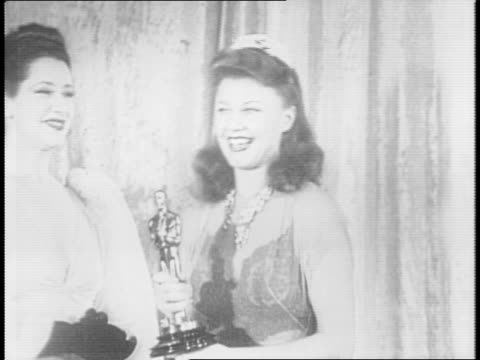 hollywood dignitaries sit at tables in black-tie dress / new mexico governor john esten miles sits with madeleine carroll / ginger rogers accepts... - academy awards stock-videos und b-roll-filmmaterial
