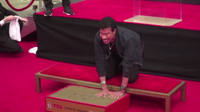 hollywood honors lionel richie as he leaves his handprints and footprints in cement in front of the tcl chinese theater in los angeles - tcl chinese theater stock-videos und b-roll-filmmaterial