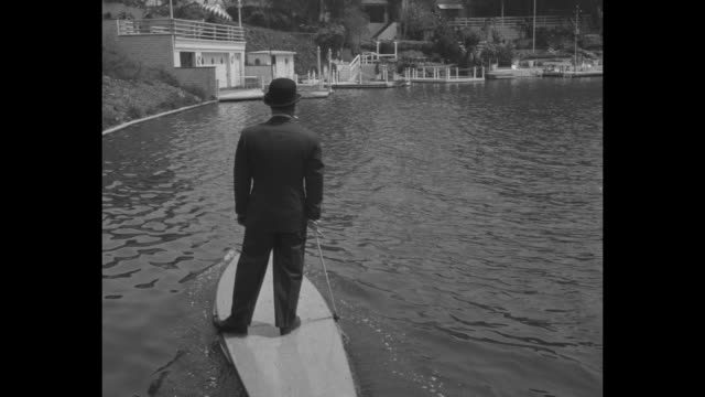VS Hollywood inventor Joe Gilpin in suit and hat and smoking a cigarette gets on his Motorboard a motorized surfboard at dock and rides it around the...