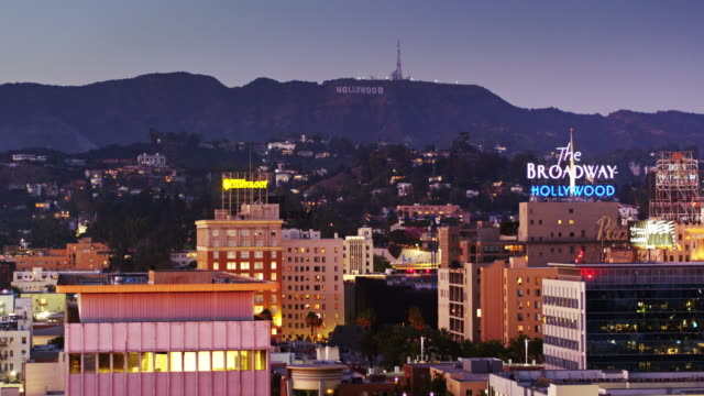hollywood lit up at night - aerial shot - city of los angeles stock-videos und b-roll-filmmaterial