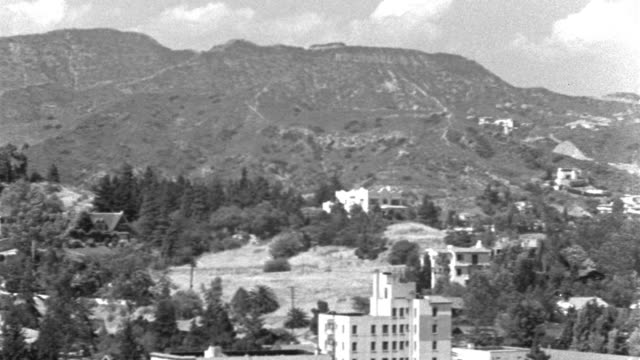 """vidéos et rushes de dx - hollywood - pan l to r over hollywood - starting on the hills ending on the blvd. (boulevard) from highland avenue toward town - b&w.  pans past """"hollywoodland"""" sign and grffith observatory. - hollywood californie"""