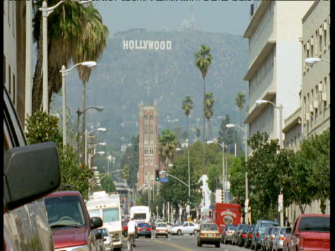 hollywood sign on hills over streets, california - hollywood california stock videos & royalty-free footage