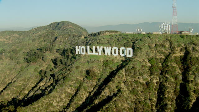 AERIAL Hollywood sign over looking Los Angeles, CA / zoom in on buildings on other side of hill