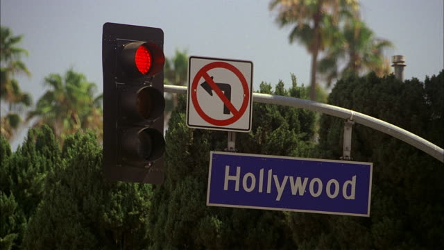 "a hollywood street sign hangs from a traffic light pole under a ""no left turn"" sign. - road sign stock videos & royalty-free footage"