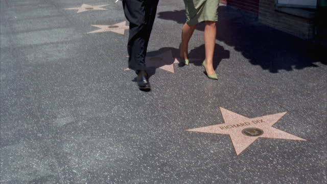 ms pan hollywood walk of fame stars in sidewalk - ウォークオブフェーム点の映像素材/bロール