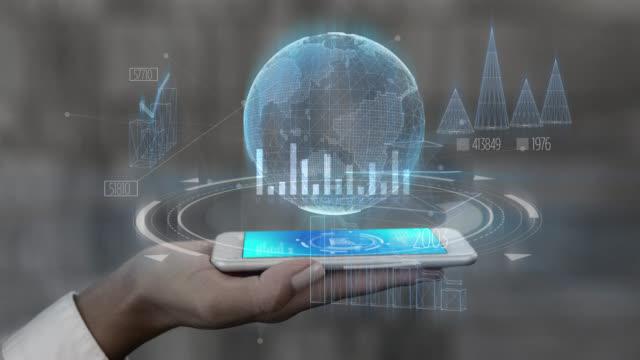 holographische schnittstelle von statistiken und daten auf dem smartphone, die von einer nicht erkennbaren person zur hand gehalten werden - erweiterte realität stock-videos und b-roll-filmmaterial