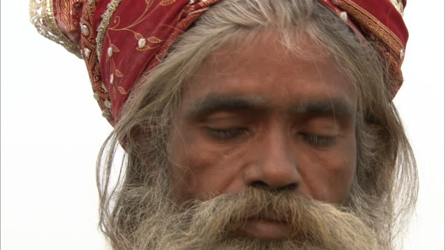 A holy man rubs ash on his forehead during a cremation ceremony.