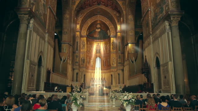 'holy rays of light' highlight a bridal party in the stunningly ornate, gilded cathedral of monreale in palermo, sicily, italy - church stock videos & royalty-free footage
