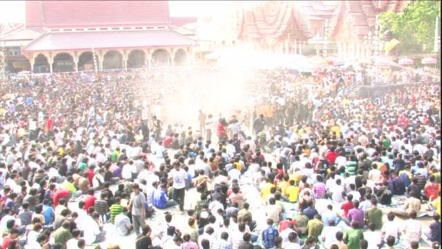 holy water sprays above a crowd of buddhists near a buddhist temple in thailand. - holy water stock videos & royalty-free footage