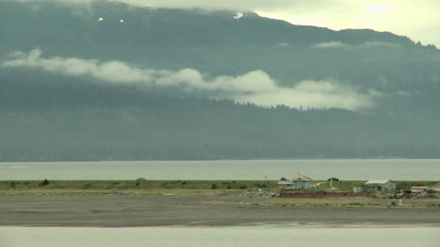 """home and shed at side of homer spit road viewed from shore of coal bay, homer, kenai peninsula, alaska.  several cars passing, looking towards kachemak bay state park and wilderness park, snow capped mountains in background."" - homer alaska stock videos & royalty-free footage"