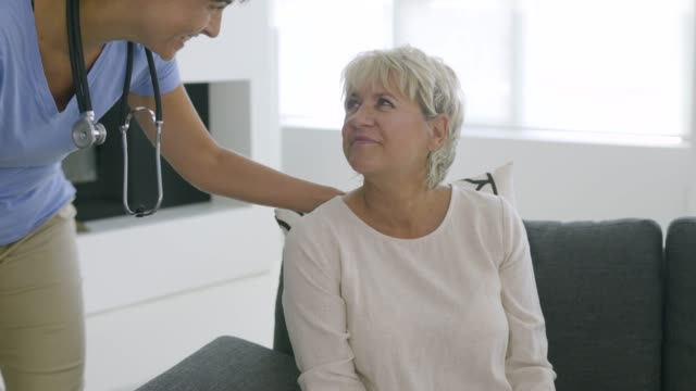 home care worker visiting with mature woman in her home. - hausbesuch stock-videos und b-roll-filmmaterial