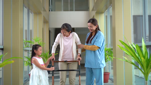 home caregiver assisting elderly woman to use walking frame - trust stock videos & royalty-free footage