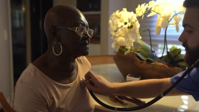 hem vårdgivare undersöker senior kvinna - social service bildbanksvideor och videomaterial från bakom kulisserna