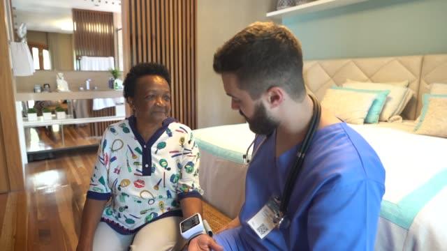 vídeos de stock, filmes e b-roll de cuidador home que examina a mulher sênior - profissional de enfermagem
