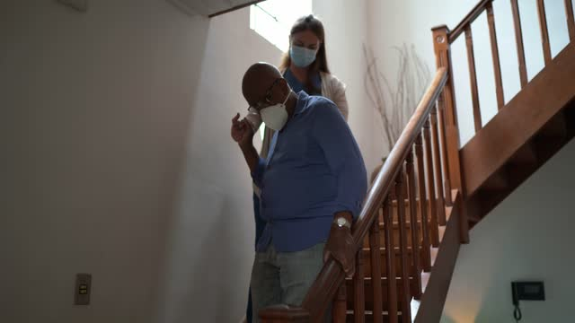 home caregiver helping senior man walking on the staris at home - wearing face mask - social services stock videos & royalty-free footage