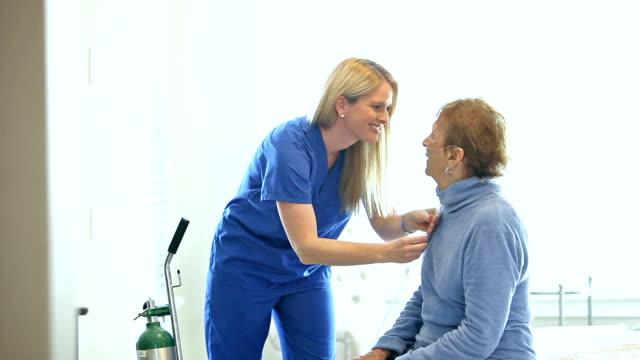 vídeos y material grabado en eventos de stock de casa cuidador ayuda a mujer senior con oxígeno - cuidador en el hogar