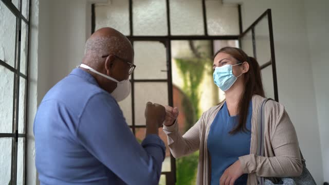 home caregiver leaving patient's house greeting with fist bump - wearing face mask - community care stock videos & royalty-free footage
