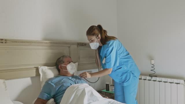 hem caregiver lyssna på vitala tecken på att återhämta senior - stetoskop bildbanksvideor och videomaterial från bakom kulisserna