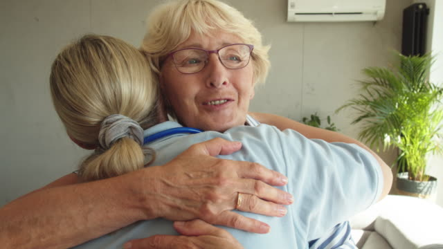 home caregiver supporting senior woman - embracing stock videos & royalty-free footage