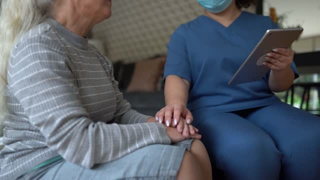 home caregiver talking to and consoling senior patient at home - social services stock videos & royalty-free footage