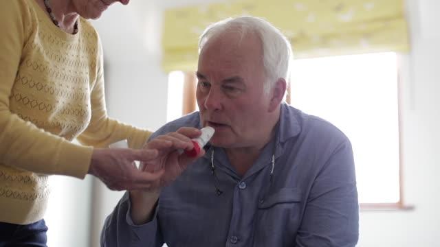Home caregiver wife gives sick husband asthma inhaler