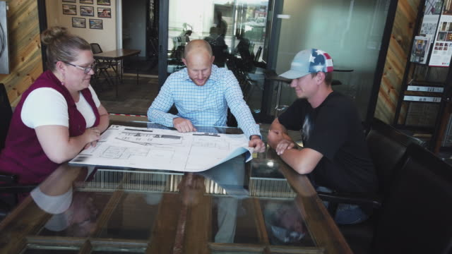 home construction staff planning meeting and reviewing house plans 4k video - permission concept stock videos & royalty-free footage