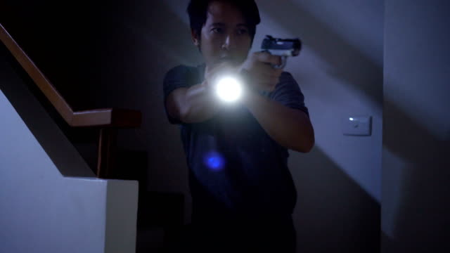 4k home defense concept, asian man holding pistol and flashlight at night. - defending stock videos & royalty-free footage