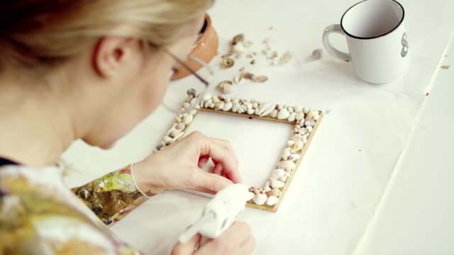 home diy. woman decorating frame. - seashell stock videos & royalty-free footage