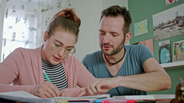 vídeos de stock, filmes e b-roll de home education and private tutoring lesson by a male tutor teaching / helping a female student while team working - praça