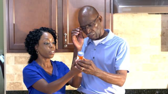 vídeos de stock e filmes b-roll de home health aid helping senior man with medication - prescription medicine