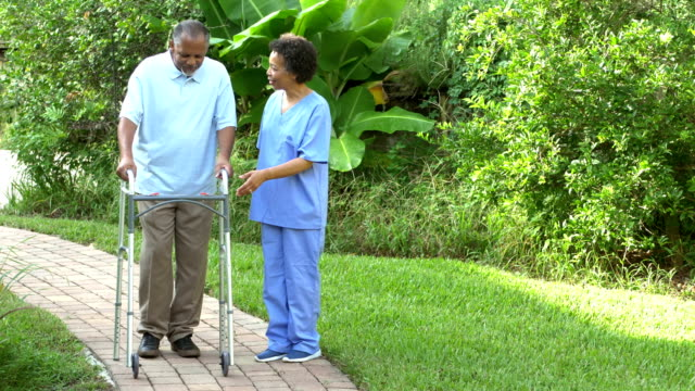 home health care nurse helping senior man with walker - walking frame stock videos & royalty-free footage