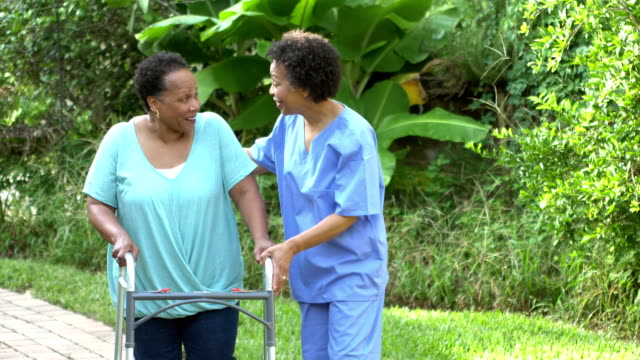 home health care nurse helping senior woman with walker - healthcare worker stock videos & royalty-free footage