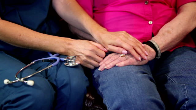 Home healthcare nurse comforts senior woman. Hands.