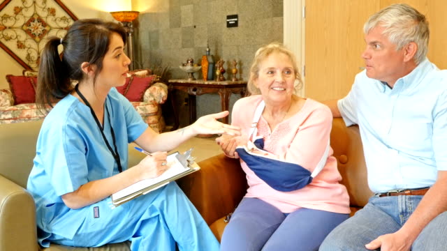 Home healthcare nurse explaining injury to senior woman and husband during appointment