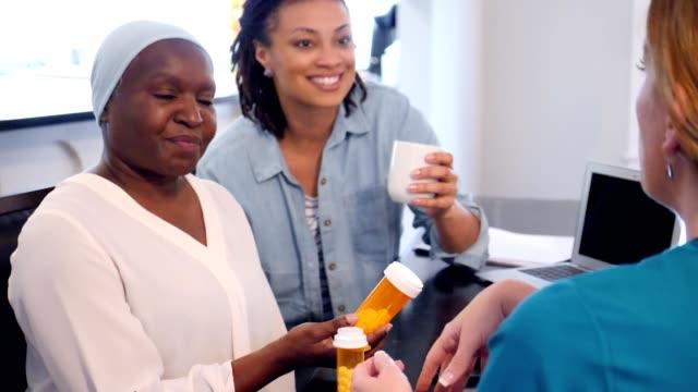 home healthcare nurse explains medication to senior patient - nurse cap stock videos & royalty-free footage
