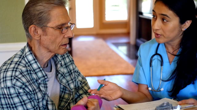 stockvideo's en b-roll-footage met huis gezondheidszorg verpleegkundige of fysiotherapeut overzichten van senior patiënt zorgplan - operatiekleding